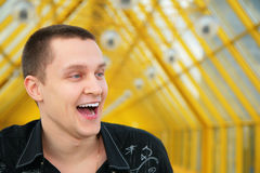 Laughing young man in black Stock Images
