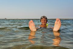 Young man floats in water with feet up Stock Photo