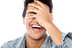Laughing young man with hand on his face Royalty Free Stock Photos