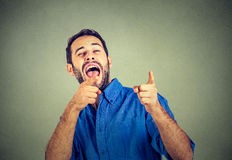 Laughing young man. Laughing young handsome man pointing at someone Stock Image