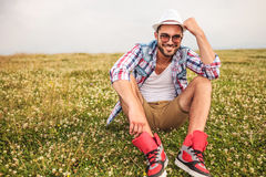 Laughing young man holding his hand on hat Royalty Free Stock Photo