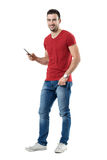 Laughing young man holding mobile phone reading humorous message. Full body length portrait isolated over white studio background Royalty Free Stock Images