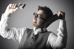 Laughing young man makes a selfie with a compact camera Royalty Free Stock Image