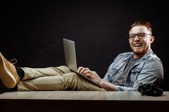 Laughing young man resing on the chair with notebook. Laughing young office worker resing on the chair with notebook at work Royalty Free Stock Photography