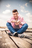 Laughing young man sitting on the floor Stock Image