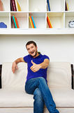 Laughing young man sitting on sofa Royalty Free Stock Photo