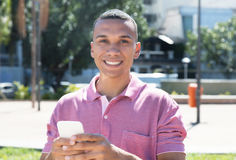 Laughing young mexican man messaging by phone. City outdoor in the city in the summer Royalty Free Stock Photography