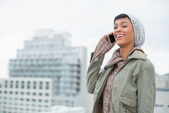 Laughing young model in winter clothes answering her phone Royalty Free Stock Photos
