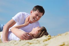 Laughing young pair lying on sand Stock Photo