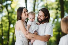 Laughing young parents dressed in the white clothes are holding daughter in the arms and looking at there son. royalty free stock photos