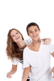 Laughing young teenagers having fun. Together with the girl draping her arm over the boy's shoulder from behind with copyspace isolated on white Stock Photos
