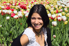 Laughing young woman. On spring tulips background Royalty Free Stock Images