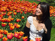 Laughing young woman. On spring tulips background Stock Photo