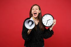 Laughing young woman in black fur sweater screaming on megaphone, holding round clock isolated on bright red wall
