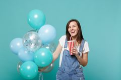 Laughing young woman in denim clothes holding plastic cup of cola or soda celebrating with colorful air balloons