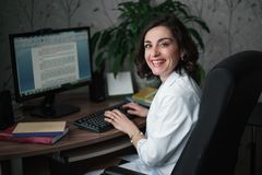 Laughing young woman doctor in a white medical robe sitting at a table. On the table books, a computer monitor and a green plant. Laughing young woman doctor in royalty free stock photo