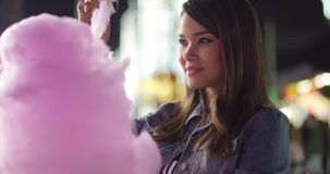 Laughing young woman eating pink candy floss stock video