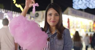 Laughing young woman eating pink candy floss stock video footage