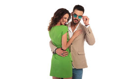Laughing young woman embracing man while he fixes his sunglasses. Laughing young women embracing men while he fixes his sunglasses ; young happy couple on white Royalty Free Stock Photo