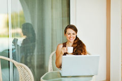 Laughing young woman enjoying cup of coffee Stock Images