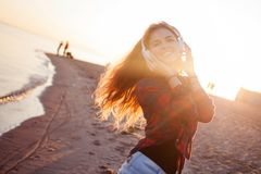 Laughing young woman enjoying the music. Portrait in bright sunset light Stock Images