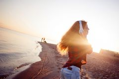 Laughing young woman enjoying the music. Portrait in bright sunset light Royalty Free Stock Photos