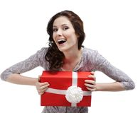 Laughing young woman hands a gift. Wrapped in red paper, isolated on white Stock Photography