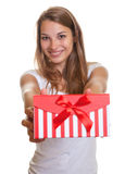 Laughing young woman hands over the christmas present Stock Photo