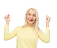 Laughing young woman with hands up Stock Photo