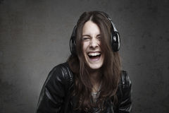 Laughing young Woman with headphones listening music Stock Photos