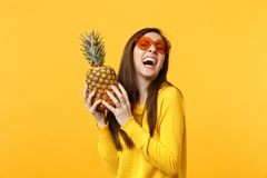 Laughing young woman in heart glasses holding in hands fresh ripe pineapple fruit isolated on yellow orange background. In studio. People vivid lifestyle, relax royalty free stock image