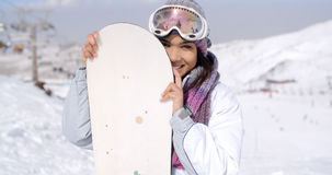 Laughing young woman with her snowboard Stock Photos