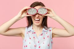 Laughing young woman holding, covering eyes with halfs of fresh ripe pitahaya dragon fruit isolated on pink pastel wall. Background. People vivid lifestyle royalty free stock images