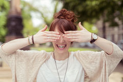Laughing young woman holding her hands to her eyes Royalty Free Stock Image