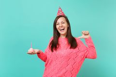 Laughing young woman in knitted pink sweater, birthday hat pointing thumb on herself holding cake with candle isolated. On blue background studio portrait royalty free stock photography