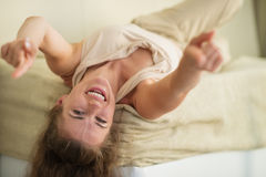 Laughing young woman laying on couch Stock Photo