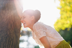 Laughing young woman lean against tree Stock Photo