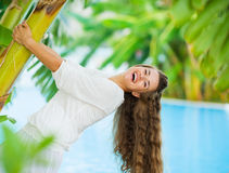 Laughing young woman leaning on tropical palm Royalty Free Stock Images