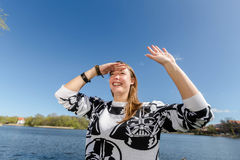Laughing young woman looks into the distance and waves Stock Image