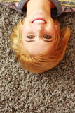 Laughing young woman lying on the carpet Royalty Free Stock Photography