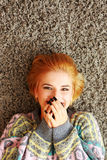 Laughing young woman lying on the carpet Royalty Free Stock Photo