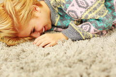 Laughing young woman lying on the carpet Stock Photos