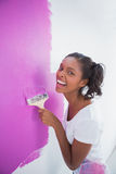 Laughing young woman painting her wall in pink Stock Photo