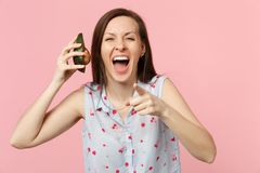 Laughing young woman pointing index finger on camera, holding half of fresh ripe avocado fruit isolated on pink pastel stock images