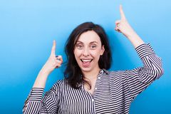 Laughing young woman pointing up with both hands. On blue background in studio Royalty Free Stock Image