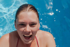 Laughing young woman in the pool, close-up portrait.  Royalty Free Stock Image