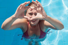 Laughing young woman in the pool shows the sign of the heart wit Stock Photos