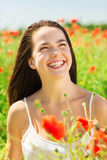 Laughing young woman on poppy field Royalty Free Stock Photo