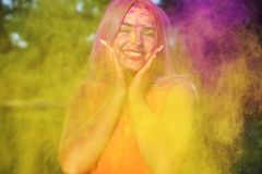 Laughing young model posing with exploding yellow paint at summer Holi festival. Laughing young woman posing with exploding yellow paint at summer Holi festival royalty free stock images