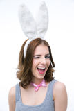 Laughing young woman in rabbit ears winking Stock Photo